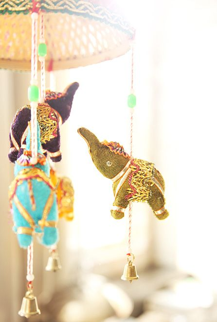 A whimsical elephant mobile with bells and beads  http://www.theglow.com/zoe-buckman/?i#8
