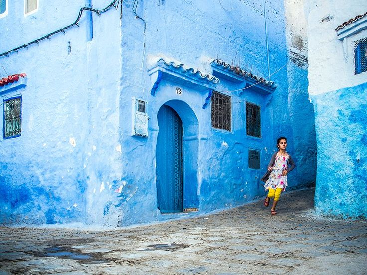 Picture of a girl running in the blue lanes of Chefchaouen, Morocco