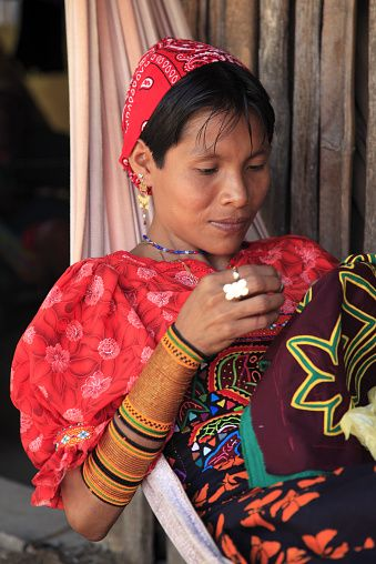 Kuna woman in traditional outfits making mola