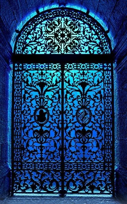 Indigo blue light through an ornate iron door frame.