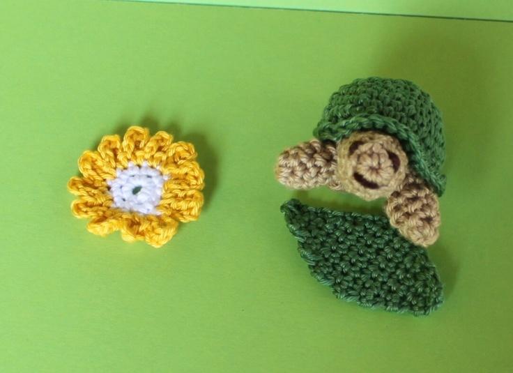 Goldige Mini-Schildkröte mit einem grünen Blatt und einer Blüte.    Diese Mini-Schildkröte sieht so niedlich aus, wie sie einen angrinst.
