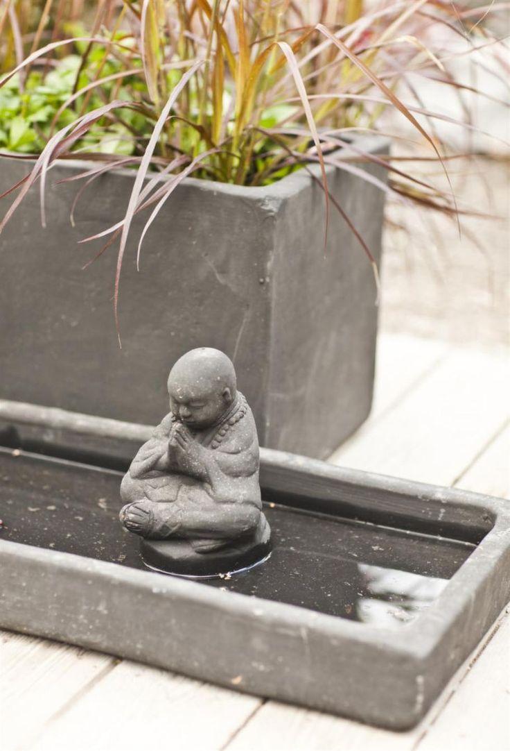 Buddha-staty och vattenspegel, kan vara inslag i en japanskinspirerad trädgård. De kommer liksom den rektangulära krukan från Zetas Trädgård.