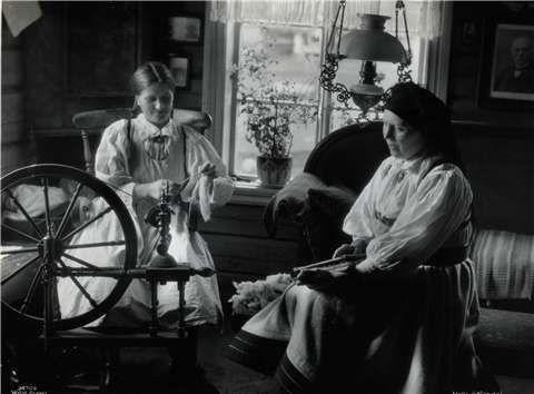 Two women spin wool in a Norwegian home. Foto: Anders Beer Wilse / Norsk Folkemuseum