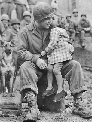 Tec. 4 Elvin Harley of Kalamazoo, Michigan, of the 3rd Armored Division, gets a peck on the cheek from a little French girl while listening to the 9th Armored Division Band near Aboncourt in northeastern France near the Belgian  border on February 14, 1945. Fighting in France was over at that point and the Battle of the Bulge had ended several weeks earlier, but the Rhine River and most of Germany lay ahead.