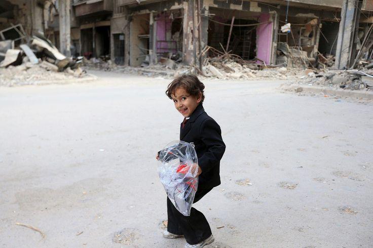 Seorang anak laki-laki membawa kantong berisi pakaian baru sebelum libur Idul Fitri yang menandakan berakhirnya Ramadan, di Jobar, pinggiran kota Damaskus, Suriah, 15 Juli 2015.