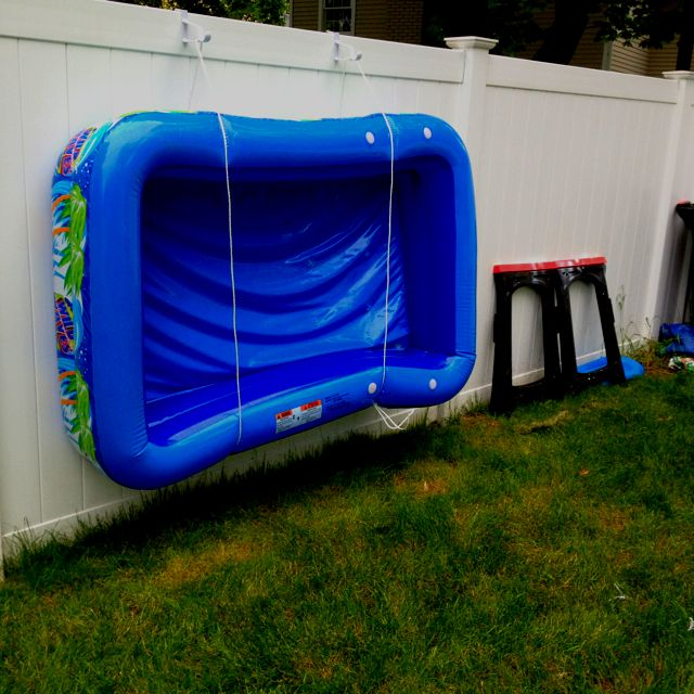 """My way of dealing with an oft used inflatable pool (drying it off, not ruining the grass, not having to deflate it all the time, etc.). Took two """"over the door"""" closet hooks and two lengths of clothesline rope tied together and hung them on the fence. Slide the pool through the two rope hoops and done."""