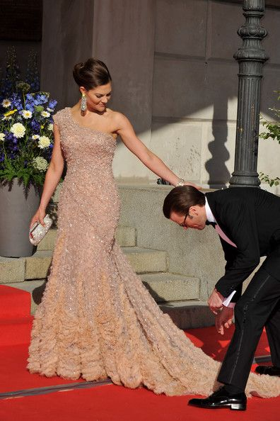 Crown Princess Victoria of Sweden is helped with her dress by fiance Daniel Westling during the Government Pre-Wedding Dinner for Crown Princess Victoria of Sweden and Daniel Westling at The Eric Ericson Hall on June 18, 2010 in Stockholm, Sweden.