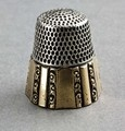 """An antique sterling silver thimble, size 10, with a panelled gold band over the sterling silver. The panelled bands alternate between larger concave panels and smaller convex panels, with a decorative floral band between each panel. The interior of the thimble is marked """"10, STERLING, and anchor"""", and the gold panelling is marked with makers mark SBC, with a large S, and smaller B and C inside the S. This is the mark for Stern Brothers & Co of Philadelphia, who were well regarded mak..."""