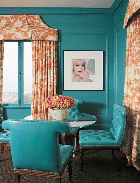 The room's lustrous sheen paves the way for other shiny elements, like this quartet of leather chairs surrounding a Lucite table. Pagoda-shaped valences above the windows echo the tangerine-and-teal chinoiserie toile itself.
