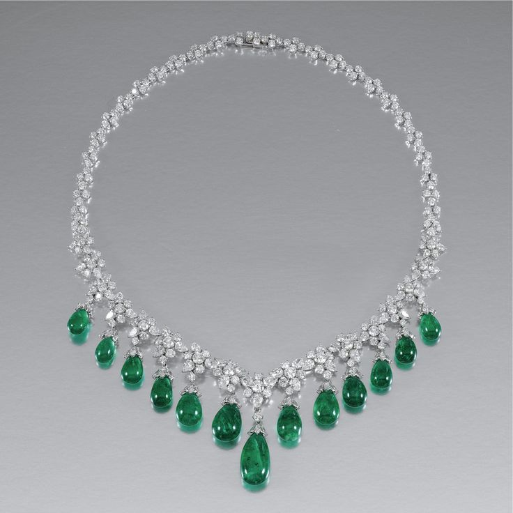 EMERALD AND DIAMOND NECKLACE, FÜRST Suspending to the front a graduated fringe of emerald drops with marquise-shaped diamond-set caps, the necklace designed as a series of stylised floral motifs, set with pear-shaped and brilliant-cut diamonds, length approximately 410mm, signed Fürst.