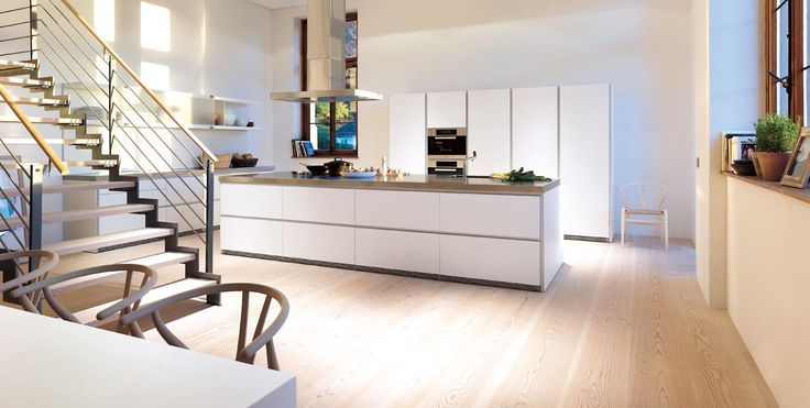 """The well-proportioned white bulthaup b1 kitchen with stainless steel worktop blends in beautifully with the """"historic"""" room, which is now totally """"lived in"""" in the truest sense of the word. The shelving system with sliding glass doors makes the area above the kitchen line particularly attractive and highly functional. The bulthaup c2 table and chairs by Hans J. Wegner complement this true family kitchen"""