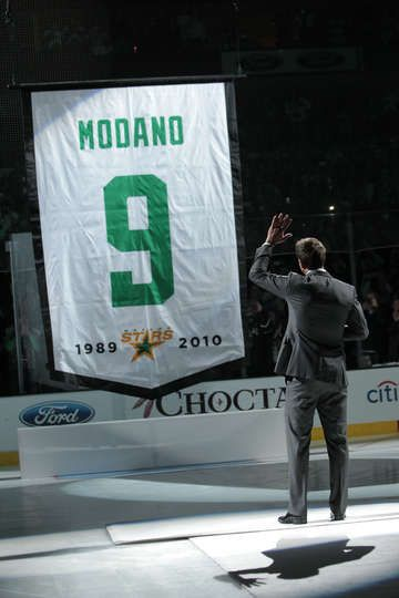 MARCH 8: Mike Modano waves to fans as his #9 jersey is hoisted to the rafters prior to a game against the Minnesota Wild at the American Air...