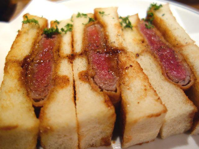 《 下北沢 》数量限定の「ビーフカツサンド」。テイクアウトも可能!  ヒレ肉を贅沢に使用したレアカツサンド  『洋食酒場 フライパン』  下北沢  こちらの看板メニューといえば分厚いヒレ肉を贅沢に使用し、レア気味に揚げられた「カツサンド」。外はカリカリ、中はふんわりもちもちのトーストに、デミグラスソースとマスタードが染みこみ、これがカツと絶妙に合う。ヒレ肉は想像以上に柔らかく、一口かぶりつけば肉汁がじゅわっと広がるのだ。   さらにこちらのカツサンドはひとつひとつがかなり分厚い。女性ならばふたつほど食べたところで、お腹いっぱいになってしまうほど。赤ワインとの相性もぴったりなので、大人のためのカツサンドと言えよう。