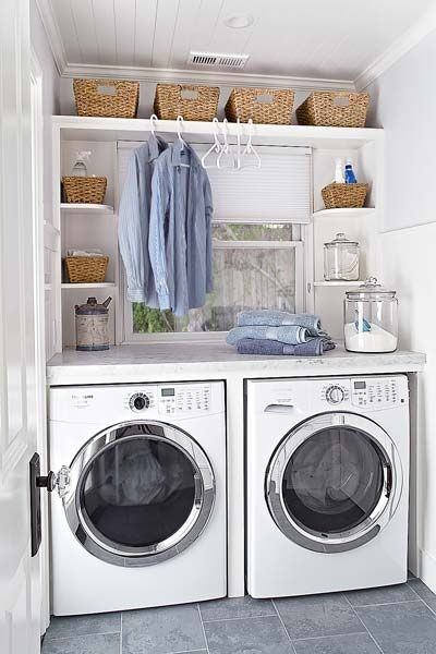 Fabulous laundry room with beadboard ceiling and gray slate tile floors. A side by side front loading Frigidaire washer and dryer pair with marble countertop and folding space. Built-in shelving flanks the window and holds seagrass baskets and laundry essentials.