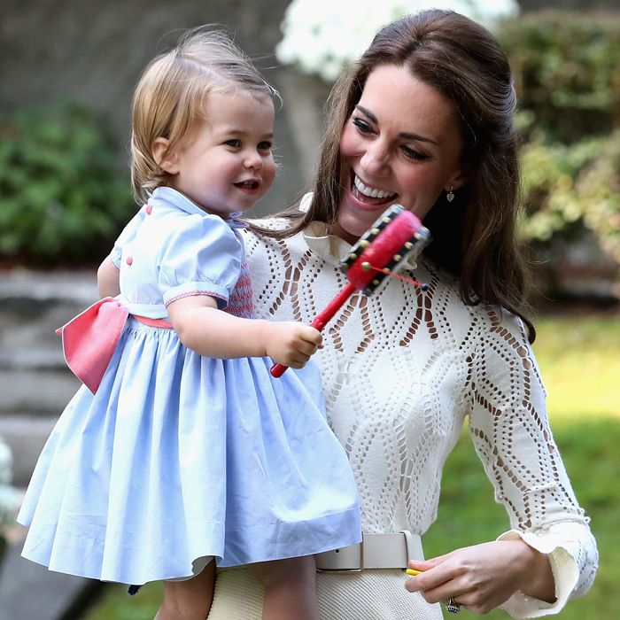 The Duchess beamed as her daughter played with a musical instrument at the party.