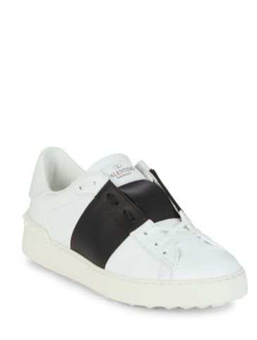 Shop now. Valentino Garavani Open Leather Sneakers. Pristine white kicks are always cool. These open trainers are a signature Valentino style: the otherwise classic low-top sneakers are updated with unexpected details – note the contrasting black panel and rubber studs running along the heel. Finished with white laces and the house logo stamped on the tongue. Wear with everything from printed dresses to laidback suiting. Effortless.
