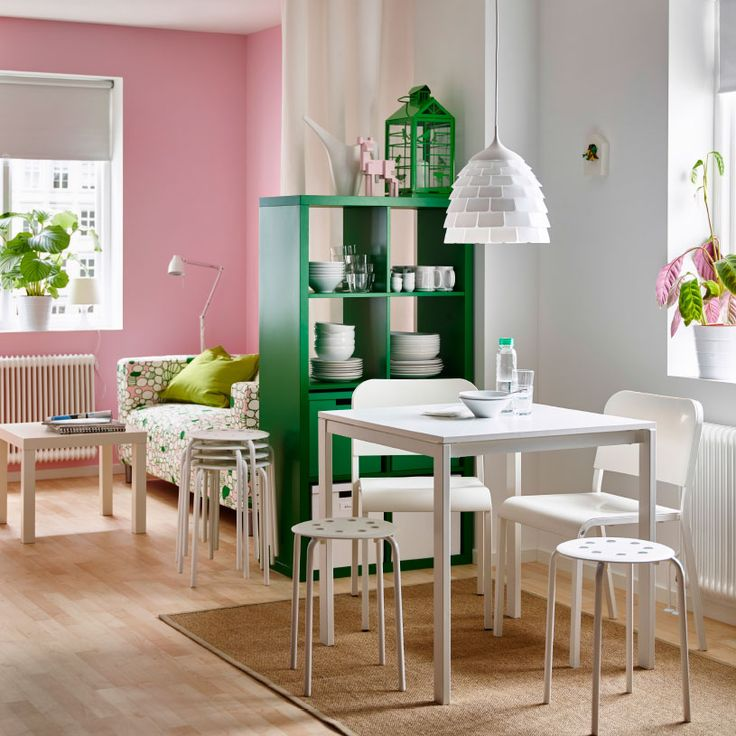 Dining Table For Two Part - 43: A Small Apartment With A Dining Area With A White Small Table And Seating,  And A Green Shelving Unit Used As A Room Divider.