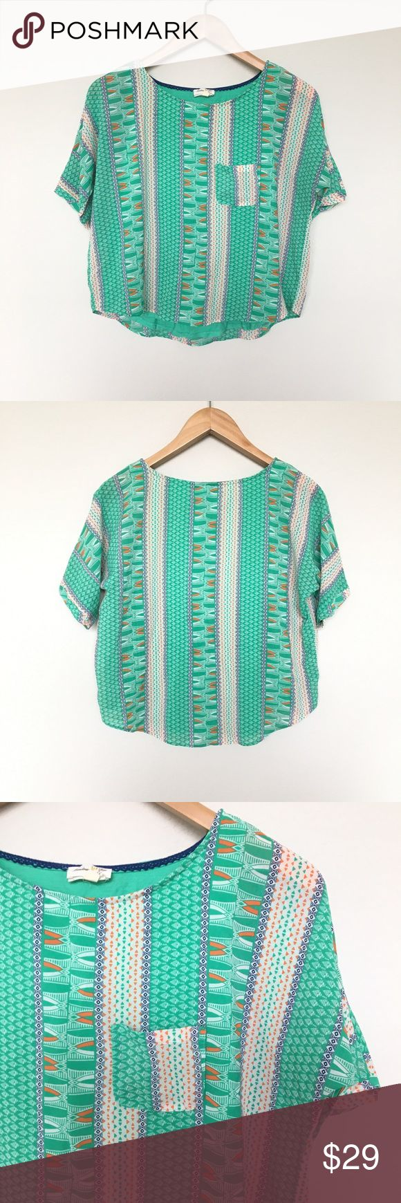 Meadow Rue Zane Geo Print Double Layer Tee 100% polyester (top layer).  60% cotton, 40% modal (bottom layer).  Gorgeous green, white and orange geo printed blouse.  Double layered that peeks out from the bottom.  Short sleeve.  Loose fit through body.  Open, slouchy chest pocket. Excellent pre-owned condition. Anthropologie Tops Blouses