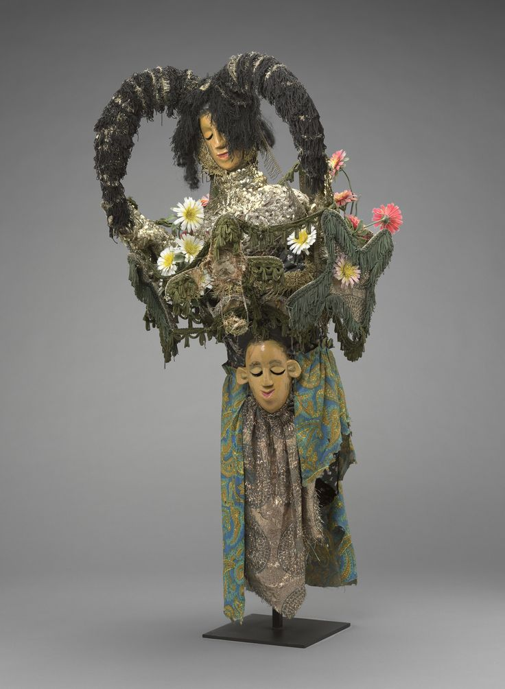Mask with Superstructure in the Form of a FemaleFigure-mid- to late 20th century Textile, wood, plastic flowers, sequins, wire, and paint. The style of the two faces on the headdress derives from the art of the Ibibio of Nigeria, who were repatriated to Sierra Leone from captured slave ships in the nineteenth century, but the pair of vertical scarification marks on each face's cheeks shows its appropriation by the indigenous Temne youth of today.
