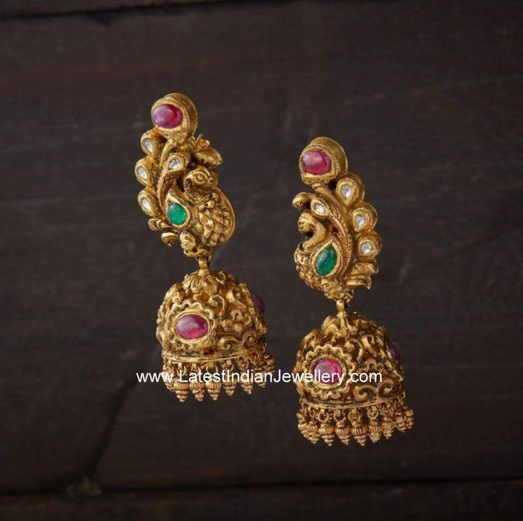 Stunningly designed antique finished gold jhumkas in intricate design. The mesmerizing peacock design eartops attached to jhumka hangings is studded with kundans.