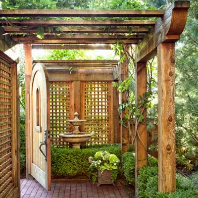 An arched wood gate, a shade arbor, a fountain, and a brick path | Photo: Mark Lohman | thisoldhouse.com