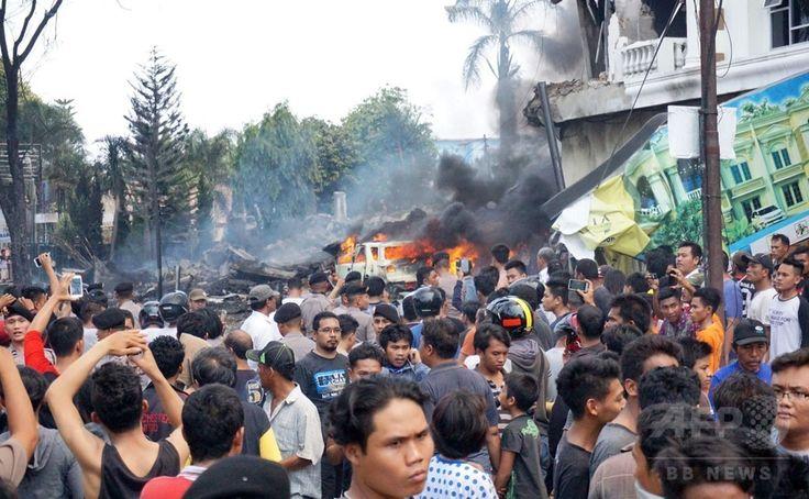 インドネシア・スマトラ島、メダンの住宅地に墜落したインドネシア軍の輸送機ハーキュリーズの残がいの周りに集まる群衆(2015年6月30日撮影)。(c)AFP/Muhammad ZULFAN DALIMUNTHE ▼30Jun2015AFP|住宅街に軍輸送機墜落、死者110人超の恐れ インドネシア http://www.afpbb.com/articles/-/3053212
