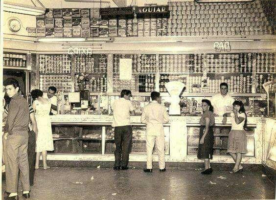 """Década de 1950 - Padaria do Aguiar no bairro do Tucuruvi. Na vitrine do balcão pode-se ver as famosas """"bengalas"""", que eram pães maiores e mais compridos. Dois tipos: a bengala suíça e a de água."""