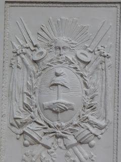 En cada una de las caras de la base del monumento se reproduce otra versión del Escudo Nacional, en los cuatro lados la misma.  Las fotos que se ven más abajo muestran tres de ellas (las caras norte, este y sur).