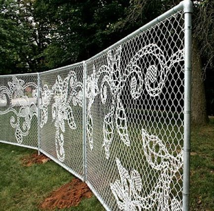 Lace yarn bomb with chain link fence.  I want this at my house!