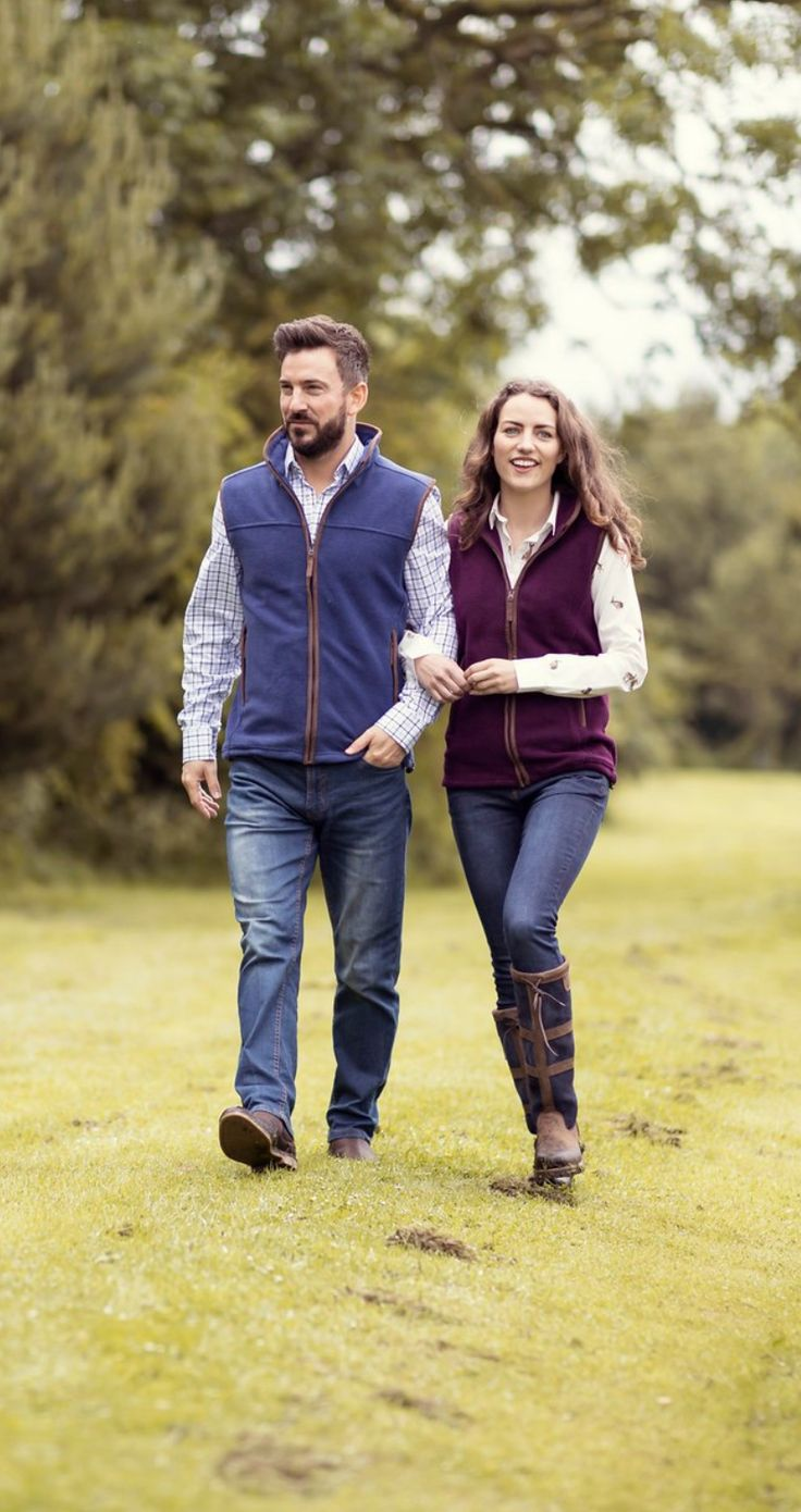 Couple in fleece waistcoats walking in the countryside
