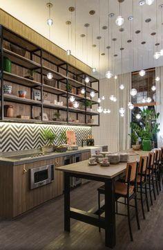 """A cozinha dentro do ambiente assinado por Marina Linhares, na edição paulistana da Casa Cor 2016, é iluminada por uma série de pendentes esféricos. Para as refeições, o balcão é amplo e acomoda cinco banquetas altas. A linguagem dos móveis tem um """"quê"""" industrial"""