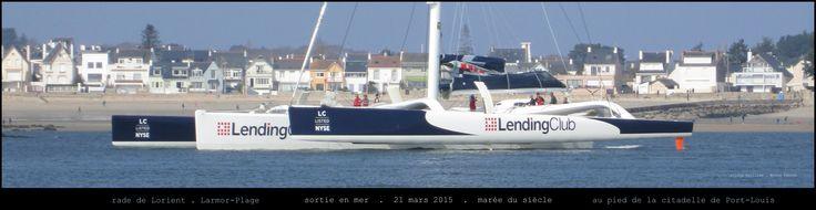 """LENDING CLUB (ancien Groupama 3), un très beau trimaran aux armes du NYSE quitte la rade de Lorient par vent arrière en cette belle matinée de """"marée du siècle"""", le 21 mars 2015. En arrière-plan : Larmor-Plage."""