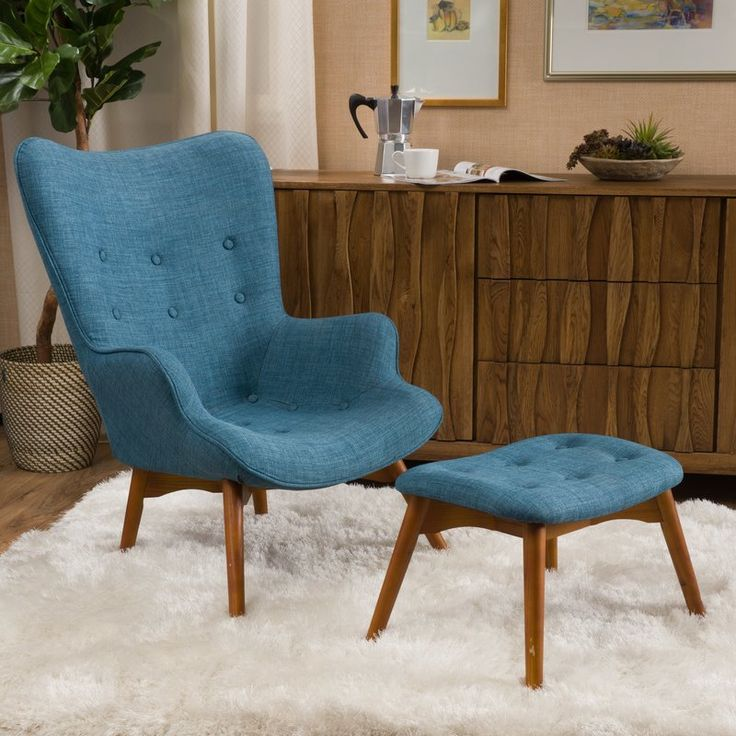 Kick your feet up in the den or give the guest suite a pop of midcentury-inspired style with this wingback chair and ottoman set, featuring button-tufted upholstery and a natural-finished wood base.