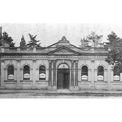 Black and white digital photograph of the Athenaeum and Mechanics Institute building, Castella Street, Lilydale. Building facade has decorative columns and double front doors, one of which is open. Posters in the front windows are printed with 'PUBLIC READING ROOM LILYDALE FREE LIBRARY'.