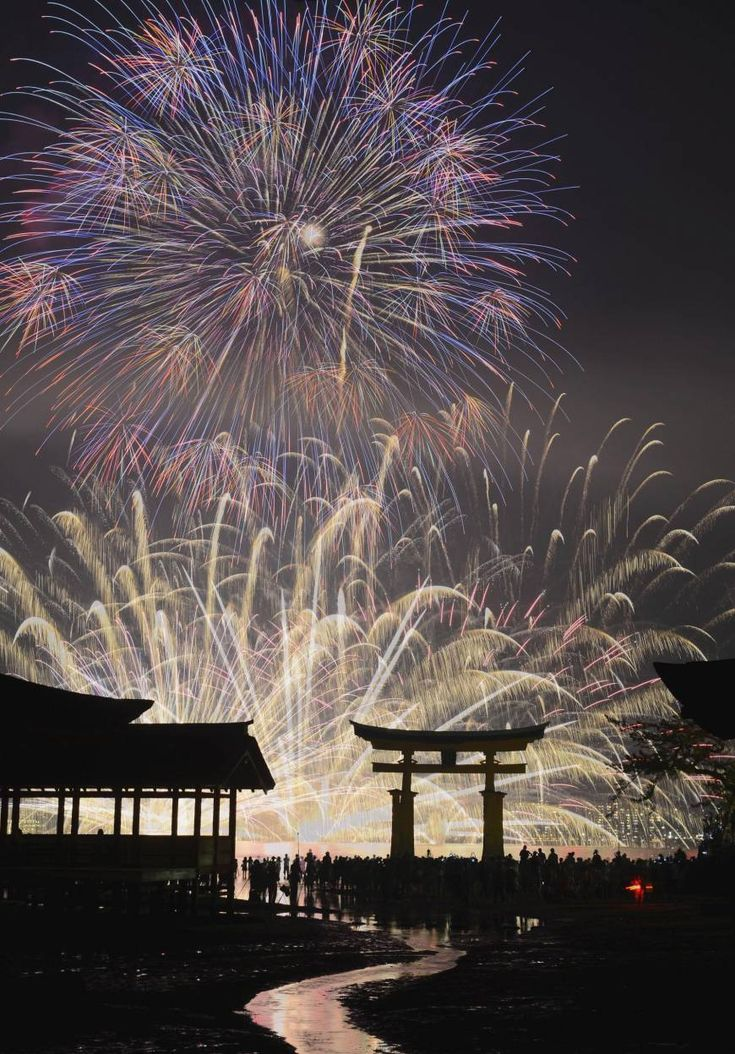 Fireworks explode over Itsukushima Shrine, which is listed as a UNESCO World Heritage Site, in Hatsukaichi, Hiroshima prefecture, western Japan Sunday, Aug. 11, 2013