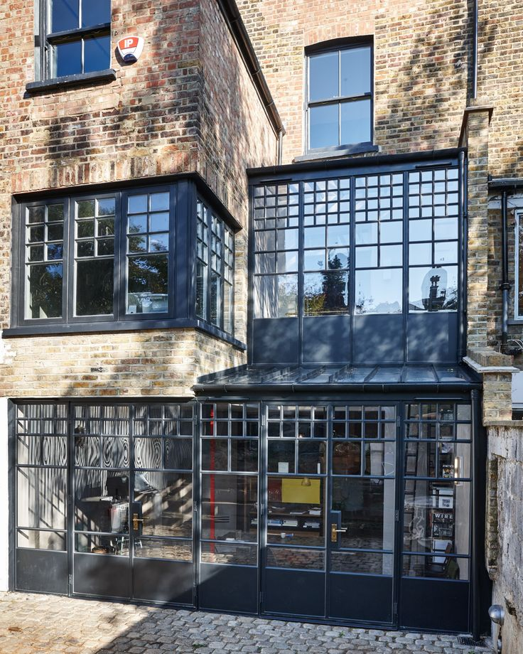 Trombe - an external photo of a double height black powder coated steel frame extension in London. A modern yet industrial style extension that has a critall style window feel and incorporates low iron glass. Doors have antique bronze Bauhaus style ironmongery