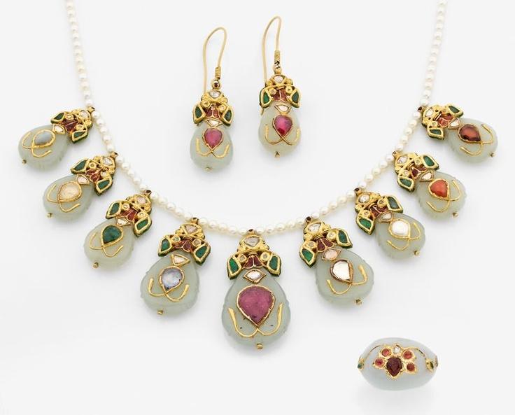 Parure composée d'un collier de perles retenant 8 poires de jade incrustées de pierres précieuses telles que : rubis, saphirs, émeraudes, chrysobéryl, corail, perle et hessonite montés sur or émaillé, une paire de boucles d'oreilles et une bague au modèle. Travail des Indes. Photo Tajan