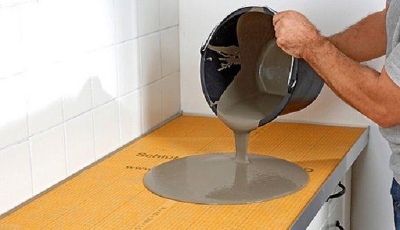 Gießen Sie die  Ausgleichsmasse in  kleineren Portionen in  die Mitte der Platte.