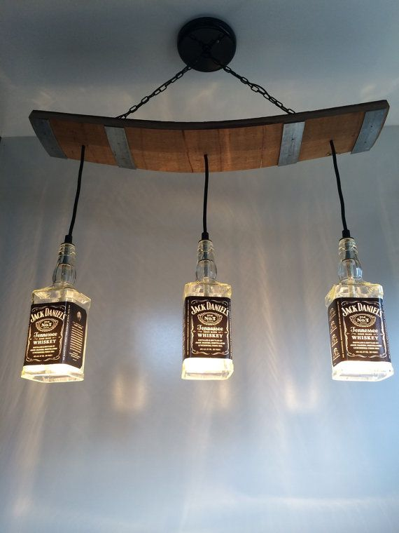 This light fixture is made from repurposed Jack Daniels bottles and wooden slats from a used barrel including the metal bands. Would be a great addition to a bar, restaurant, pool table, man cave or anywhere you need some cool lights! Actual fixture could vary slightly from pictures shown. The three liquor bottle lights are attached to a reclaimed barrel and hang from a ceiling mount by decorative black chain. Includes hardware to attach to a 4 ceiling receptacle.  Total length from ceiling…