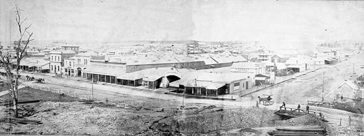 Bendigo,Victoria,circa 1857.  Looking down on the corner of Pall Mall and Mitchell Streets Bendigo. Among the shops are: the Bendigo Beehive Stores, A. Steele, Plumber, K. Knight, Saddler and Moran & Company. There is bridge over Bendigo Creek on the right.
