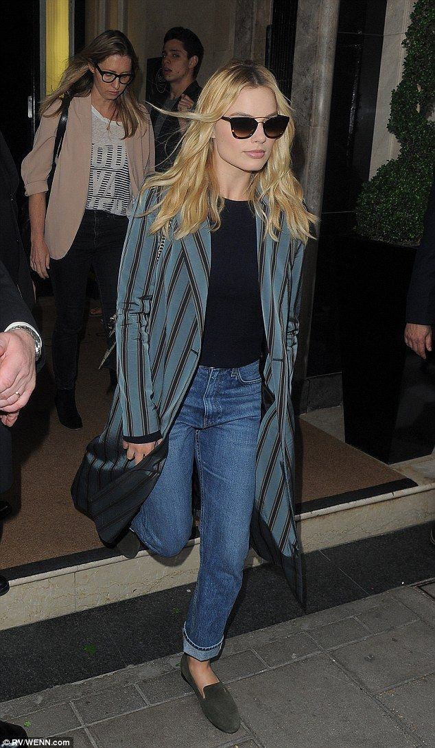 Low-key: Margot Robbie kept things casual in a long coat and flat slip-ons...