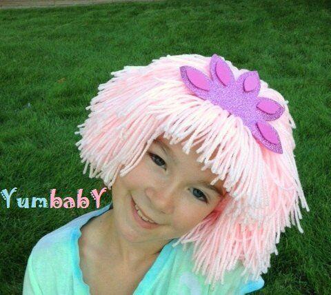 Fillette portant une amusante perruque rose en laine, avec une couronne violette et magenta.  Lalaloopsy