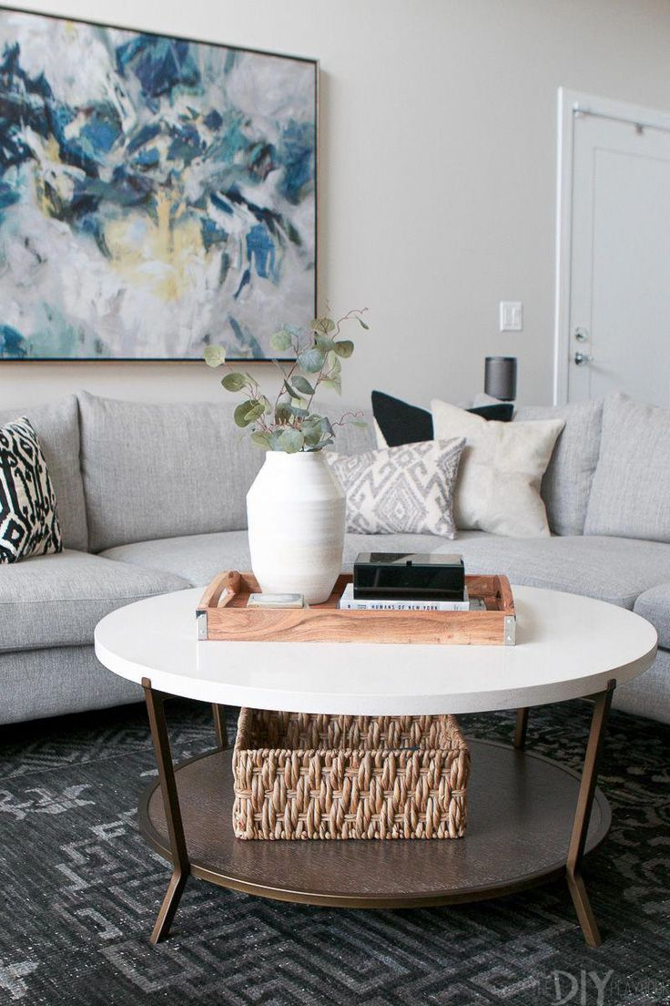 A round coffee table next to a large gray sectional love