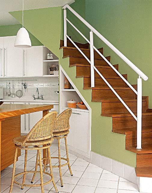 Na ampliação da cozinha, a arquiteta incorporou a área da antiga lavanderia (que, por sua vez, foi para o piso superior). Para interligar os dois ambientes, instalou-se a escada de concreto com degraus de peroba. Na parte onde o vão inferior é mais baixo (entre 0,90 e 1,60 m de altura), foi colocado o armário feito sob medida que acompanha o caimento da escada. Armários planejados com alturas variadas ocupam o espaço sobre a pia. Projeto de Paola Ribeiro.
