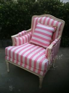 french bergère armchair: an upholstered chair having closed, upholstered sides, arm rests, seat, and back. It also includes exposed carved wooden legs.