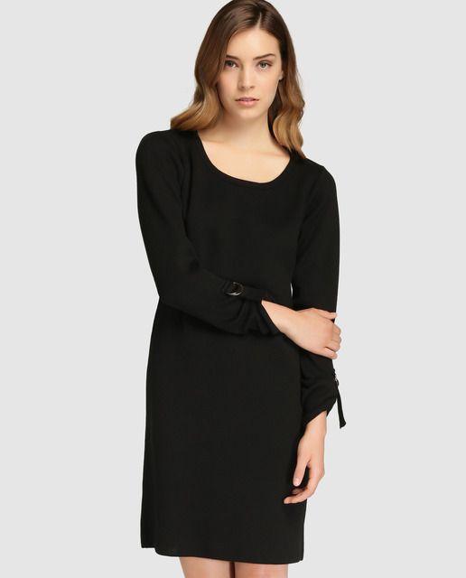 Vestido corto, tipo túnica, en color negro liso. Tiene manga larga y escote redondo.