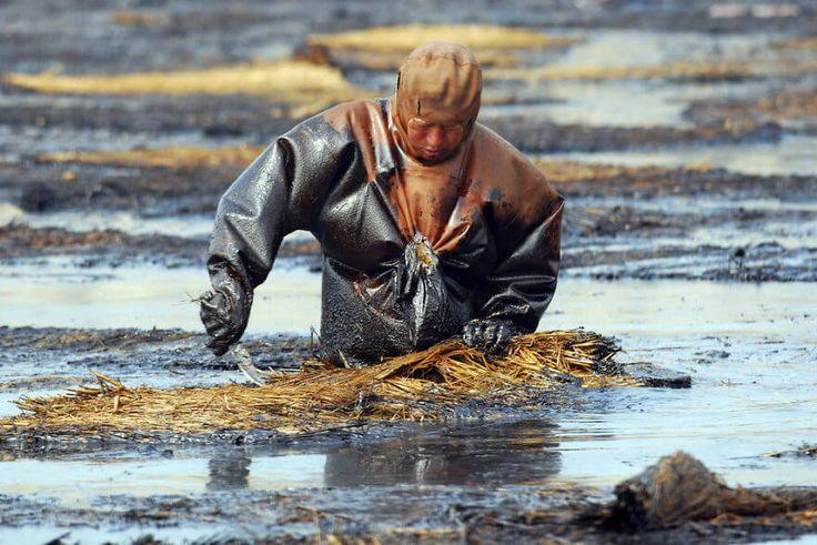 Un travailleur tente de nettoyer l'eau d'une rivière suite à un déversement de pétrole