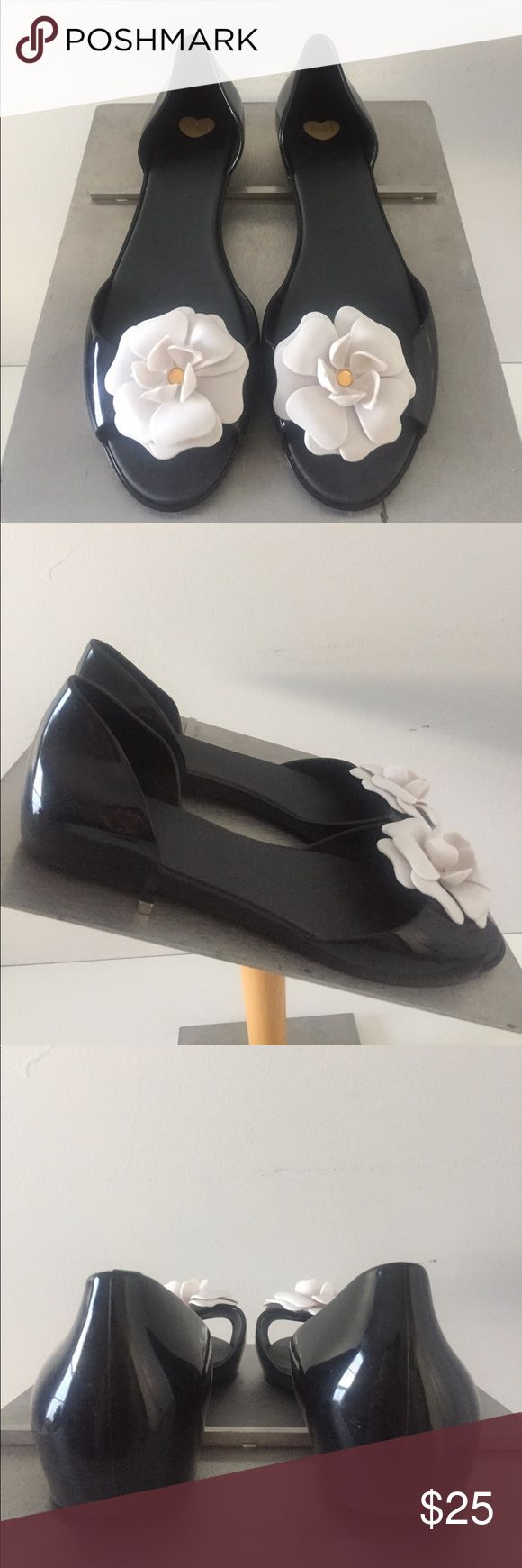 Melissa Jelly Flats Melissa is known for make a stylish jelly shoe.  Open toe flats have a white flower across the forefoot, adding a chic appeal.  Minor, minor, minor scuffs that does not kill the shoes beauty.  Wear from spring to fall. Melissa Shoes Flats & Loafers