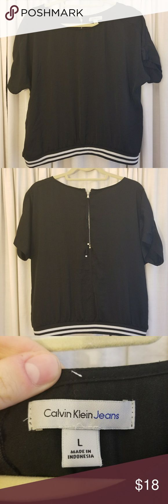 Calvin Klein athletic-style shirt Black, boxy-fit, silky athletic top with white and black banded bottom. Back zip closure. Purchased at Macy's in August 2017. Worn twice. Calvin Klein Jeans Tops Tees - Short Sleeve