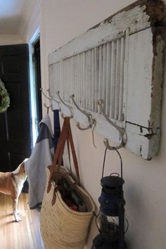 An old shutter turned horizontally and peppered with silver garment hooks transforms into a cottage-style coat rack.